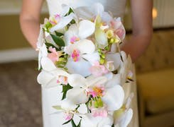 Stunning white orchids in the arms of a beautiful bride